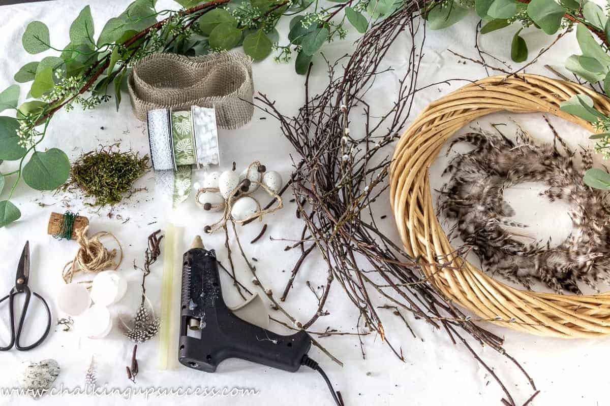 Materials needed to make a DIY spring wreath - glue gun, wreath bas, twigs, eucalytus garland, scissors, feather, eggshells and ribbons.