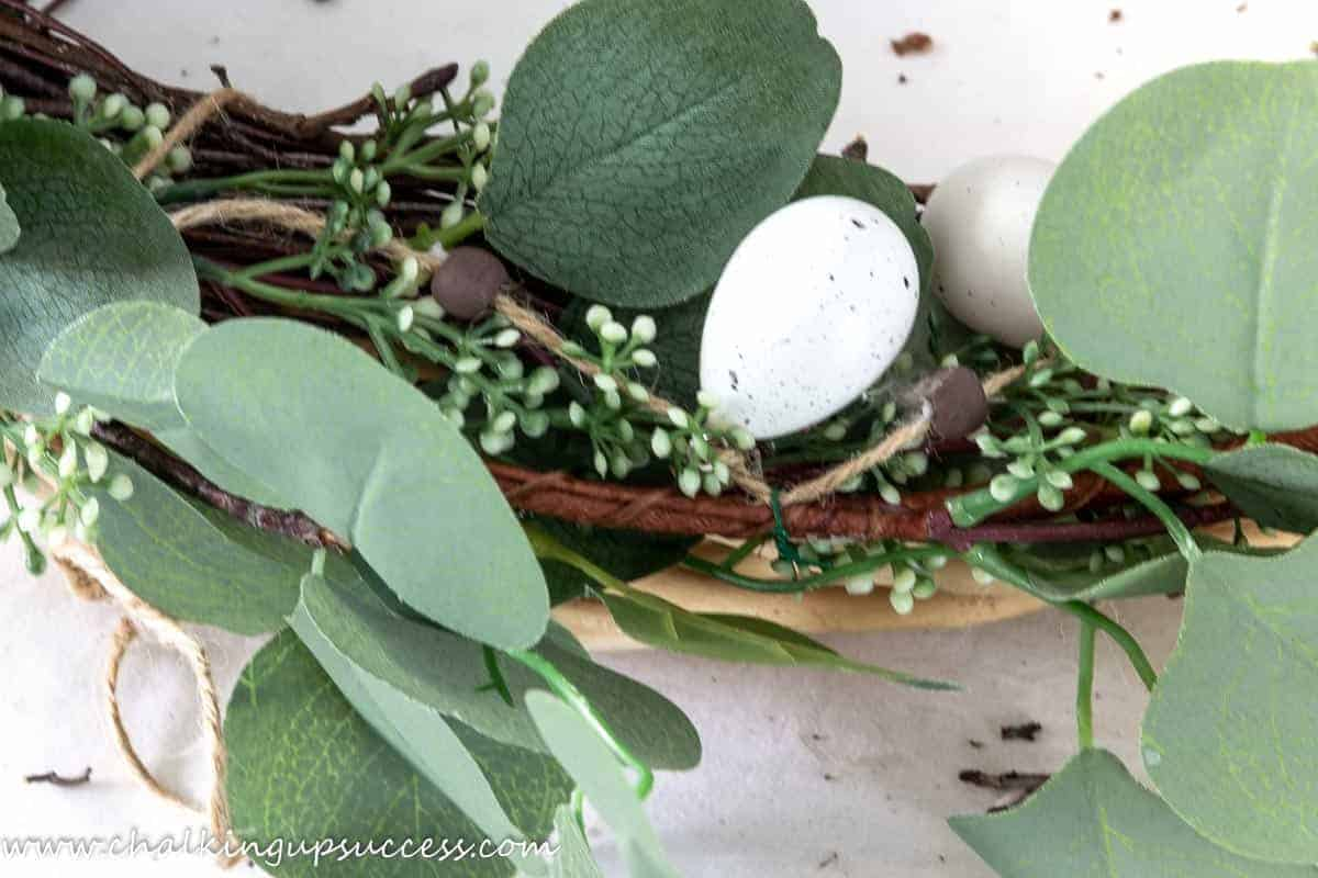 A close-up of a DIY spring wreath showing how the Easter garland has been attached to the DIY spring wreath.