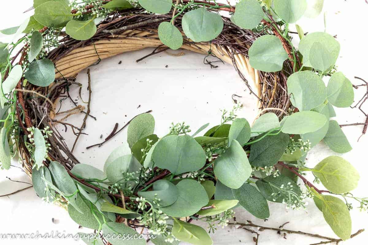 showing a DIY spring wreath - base wreath covered with a layer of twigs, and a eucalyptus garland.