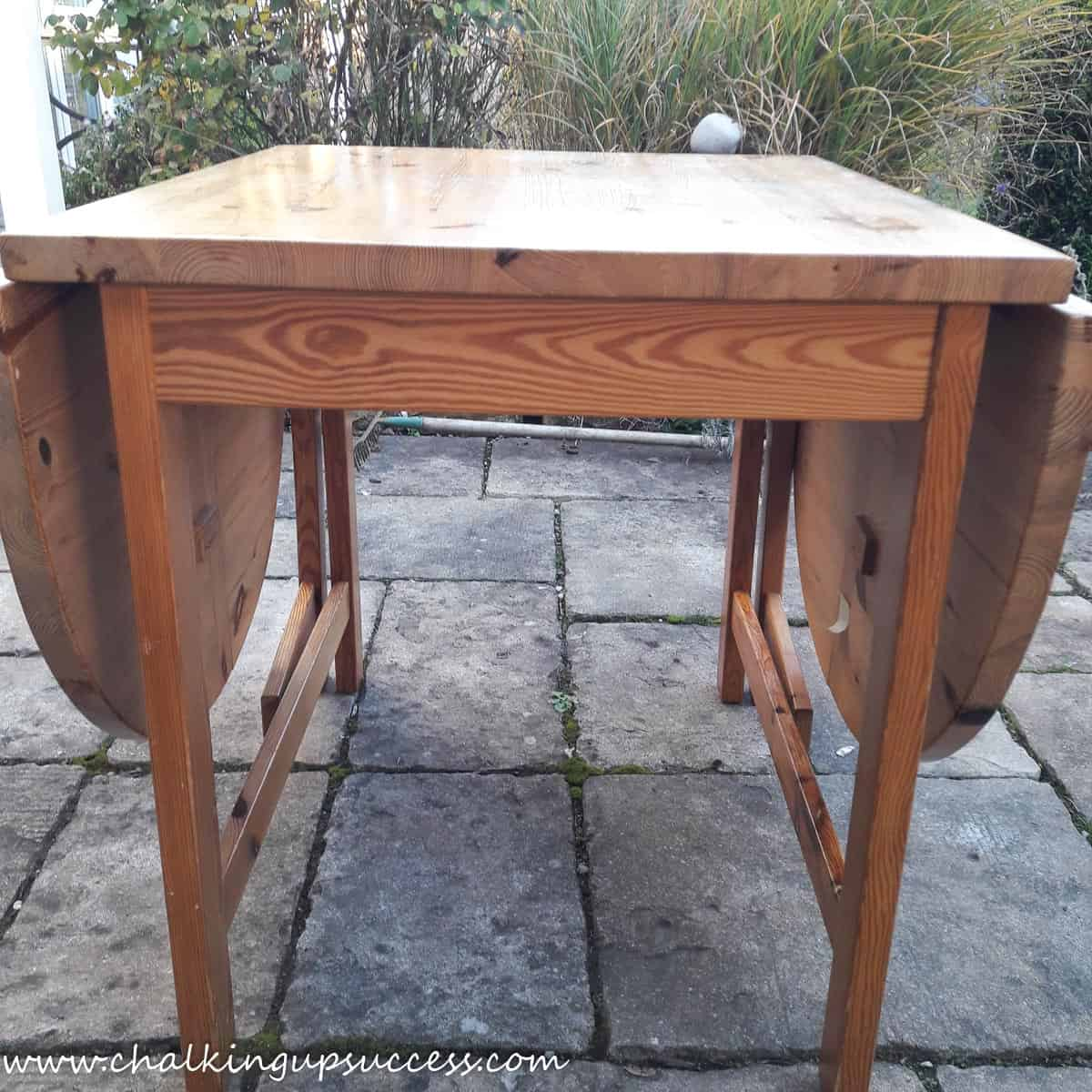 The pine table before whitewashing with chalk paint. The wood looks very orange and the tabletop is scratched.