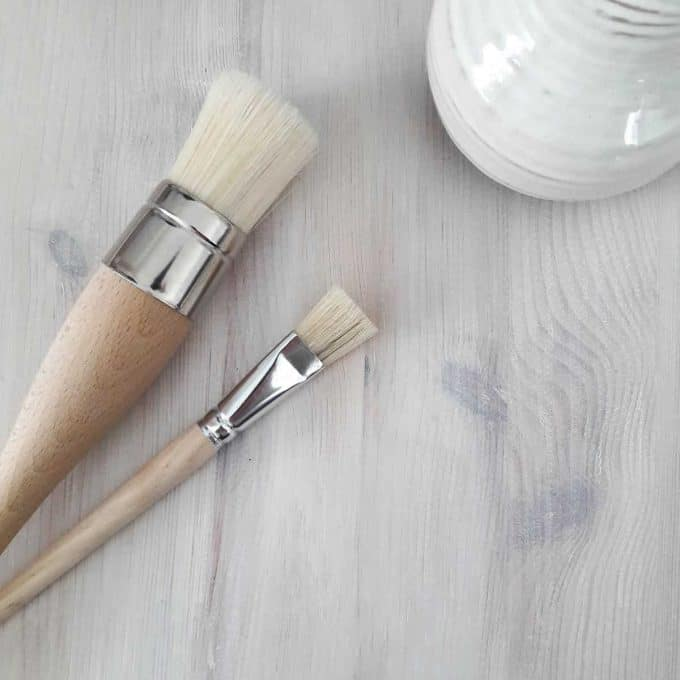 A large and small paint brush displayed on a whitewashed wood tabletop. Showing the end result of whitewashing the wood with chalk paint.