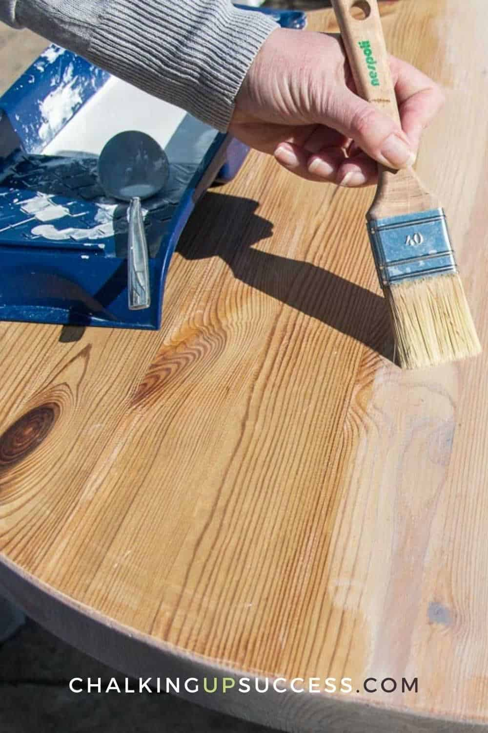 Save this pin to Pinterest. A person showing how to whitewash wood with chalk paint. Brushing on the chalk paint wash.