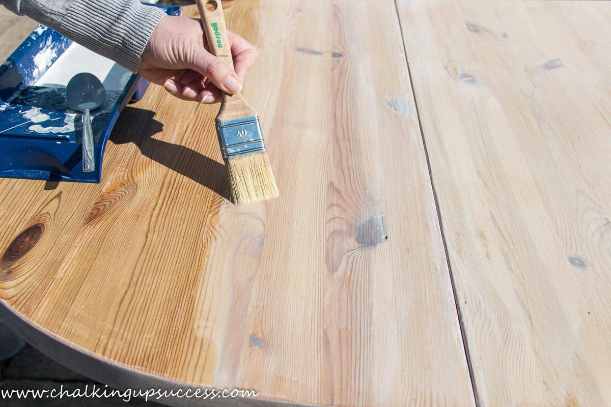 A person showing how you can whitewash wood with chalk paint. Brushing the diluted chalk paint onto the pine table.