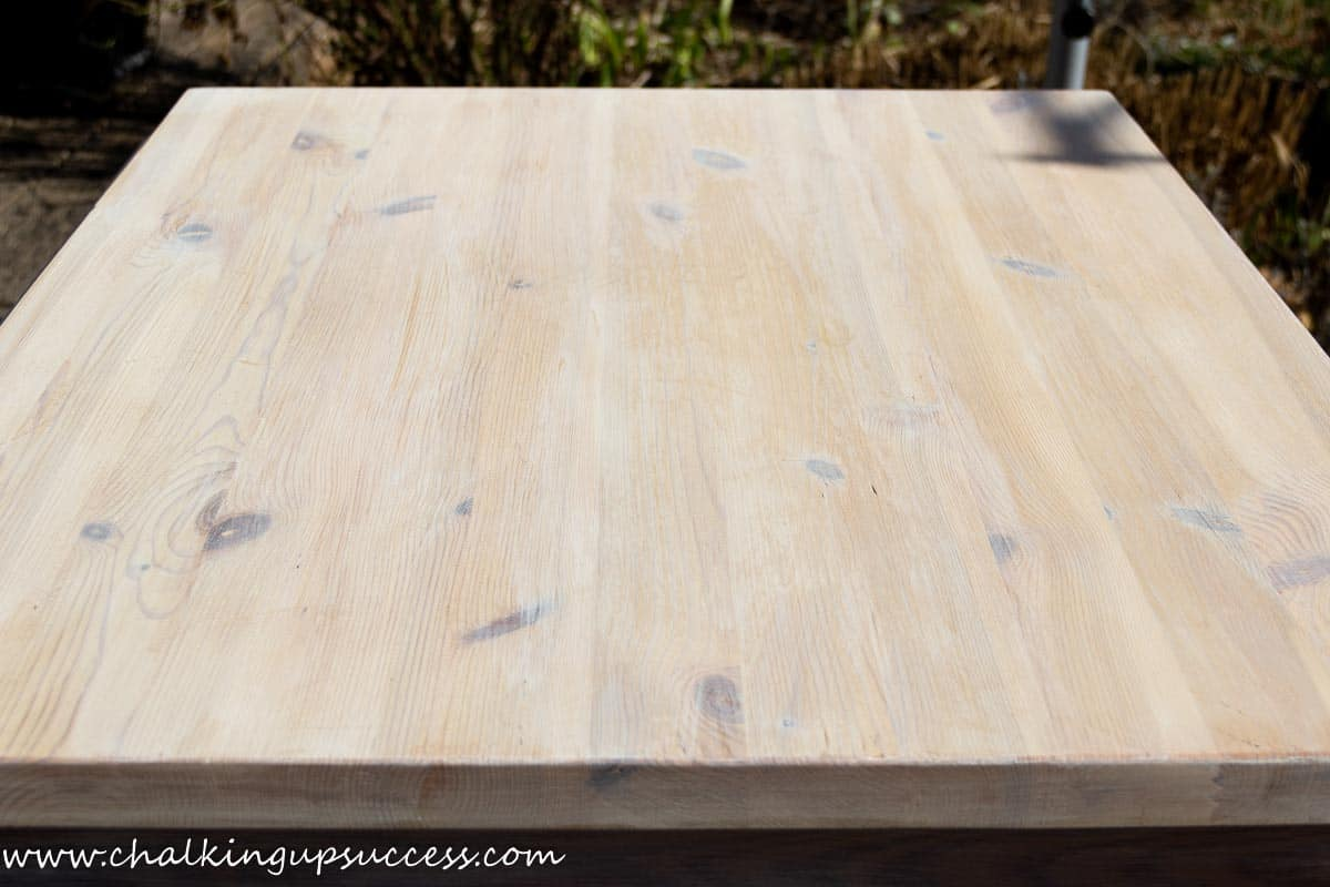 Shows the pine tabletop after one coat of the chalk paint wash. To achieve the whitewash wood affect, more layers of whitewash are needed.