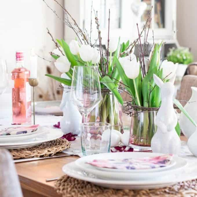 Pretty spring home tour tablescape with Easter bunnies, Easter eggs and vases filled with white tulips