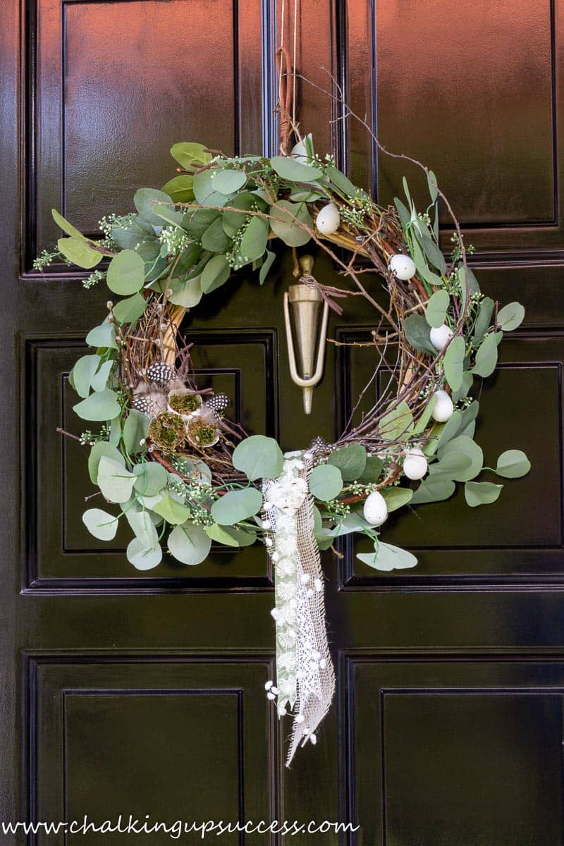 A DIY Spring wreath hanging on a black front door.