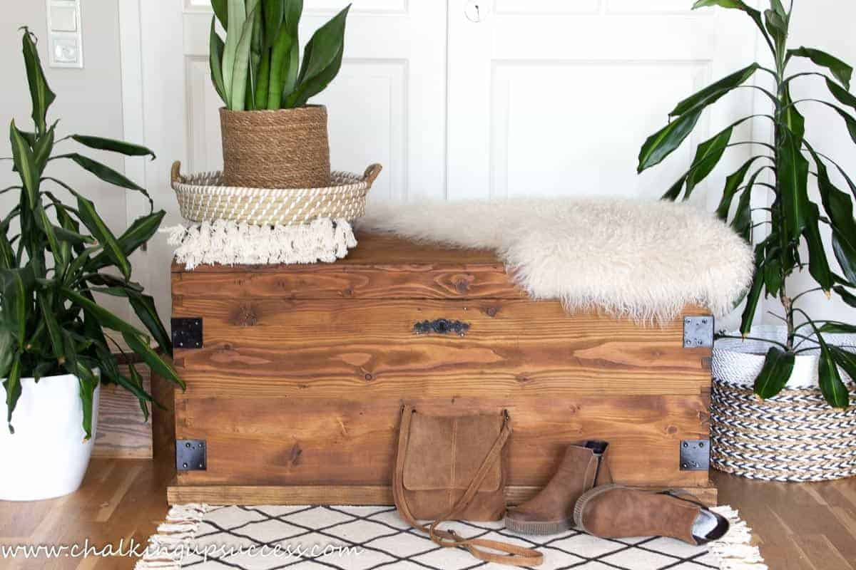 This upcycled wooden trunk, has had black metal corner brackets added. The trunk has been stained with 'oak' woodstain. A cream sheepskin rug is draped over one corner. A green sansivira plant in a sisal plant holder sits inside a natural seagrass tray which is placed on the left side of the trunk. A pair of ladies' brown suede ankel boots and a brown suede cross-over bag, lie casually next to the wooden trunk.
