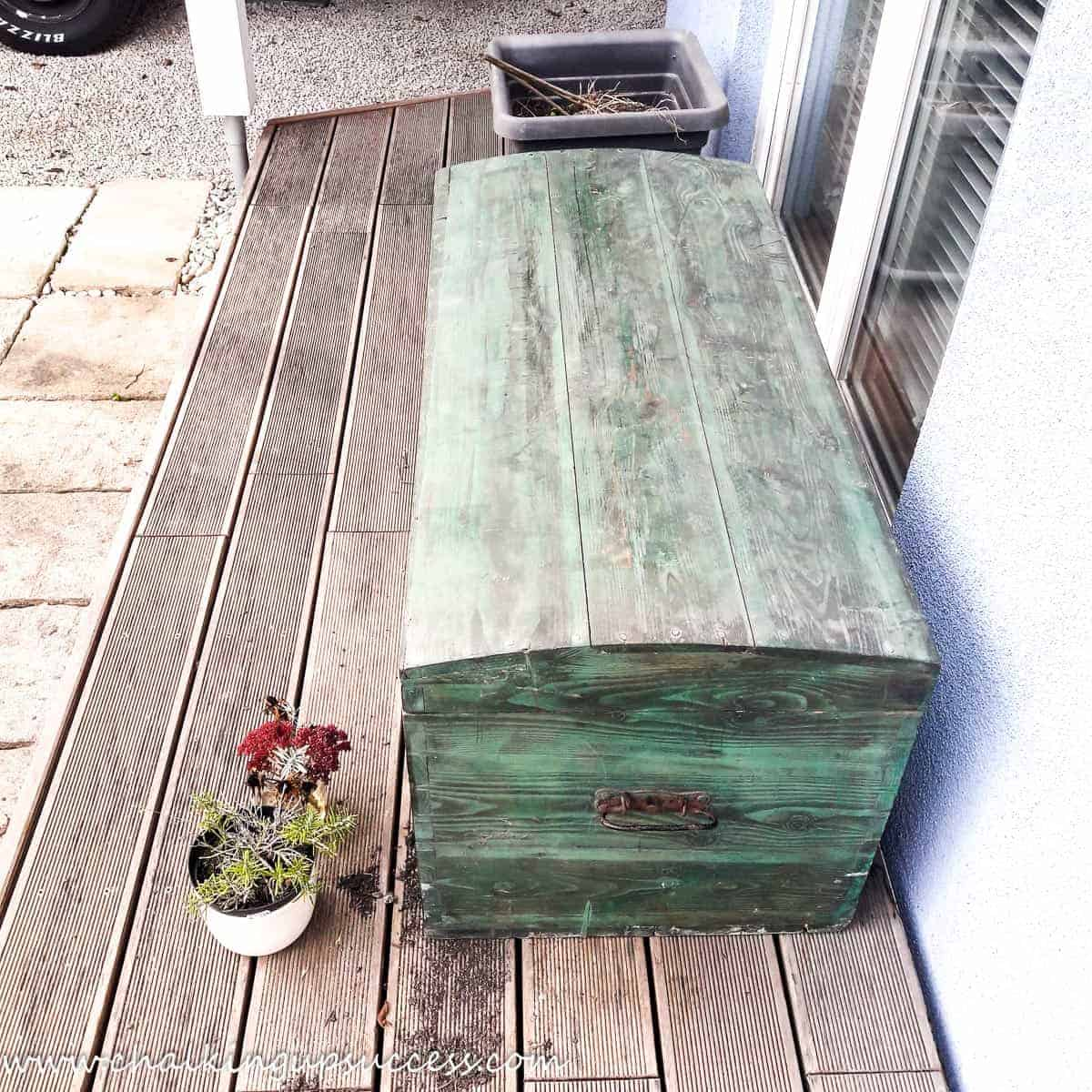 A 'before' shot of the wooden trunk on the wooden deck outside our house. The trunk has a dark green woodstain and is ver dirty after being stored in a lock-up garage for such a long time.
