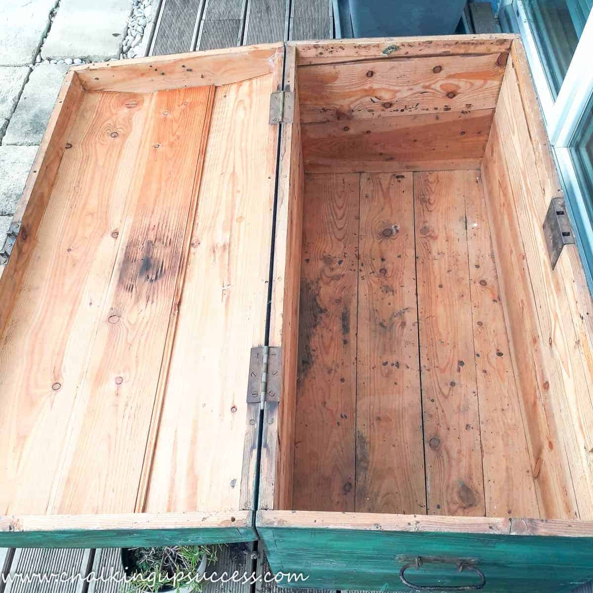A 'before' shot of the wooden trunk with the lid wide open. Inside the trunk is dirty, has nails sticking out and lots of patches of old glue.