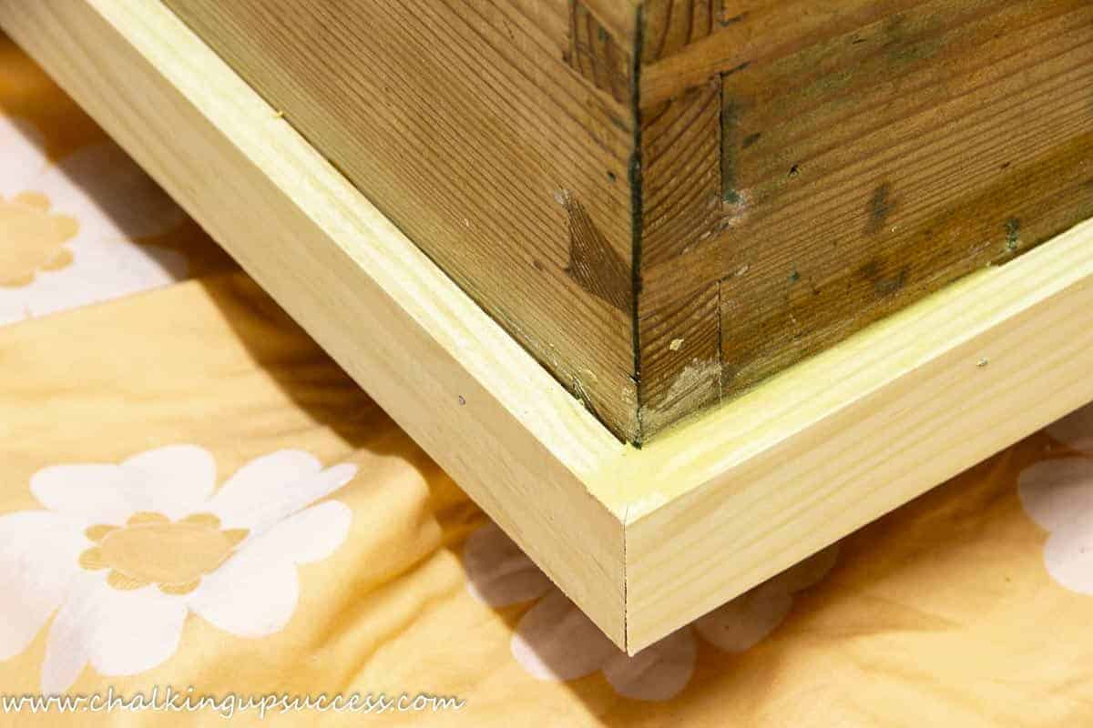 A close-up of the narrow wooden trim which has been glued and nailed around the bottom of the wooden trunk.