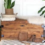 This upcycled wooden trunk, has had black metal corner brackets added. The trunk has been stained with 'oak' woodstain. A cream sheepskin rug is draped over one corner. A green sansivira plant in a sisal plant holder sits inside a natural seagrass tray which is placed on the left side of the trunk.