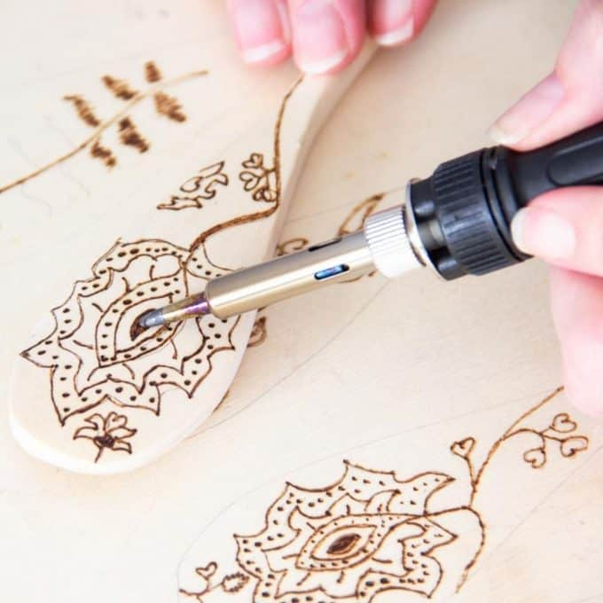 A persons hands using a pyrography tool to make wood burned spoons