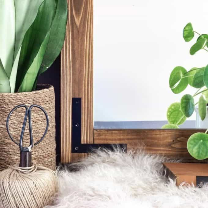 The - DIY wood framed mirror finished. Styled with green plants and baskets.