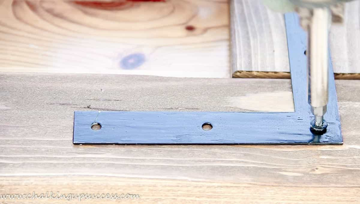 Close-up of a corner of the DIY wood framed mirror. Shows a person using a screwdriver to attach the first screw to the corner of the L-shaped bracket.