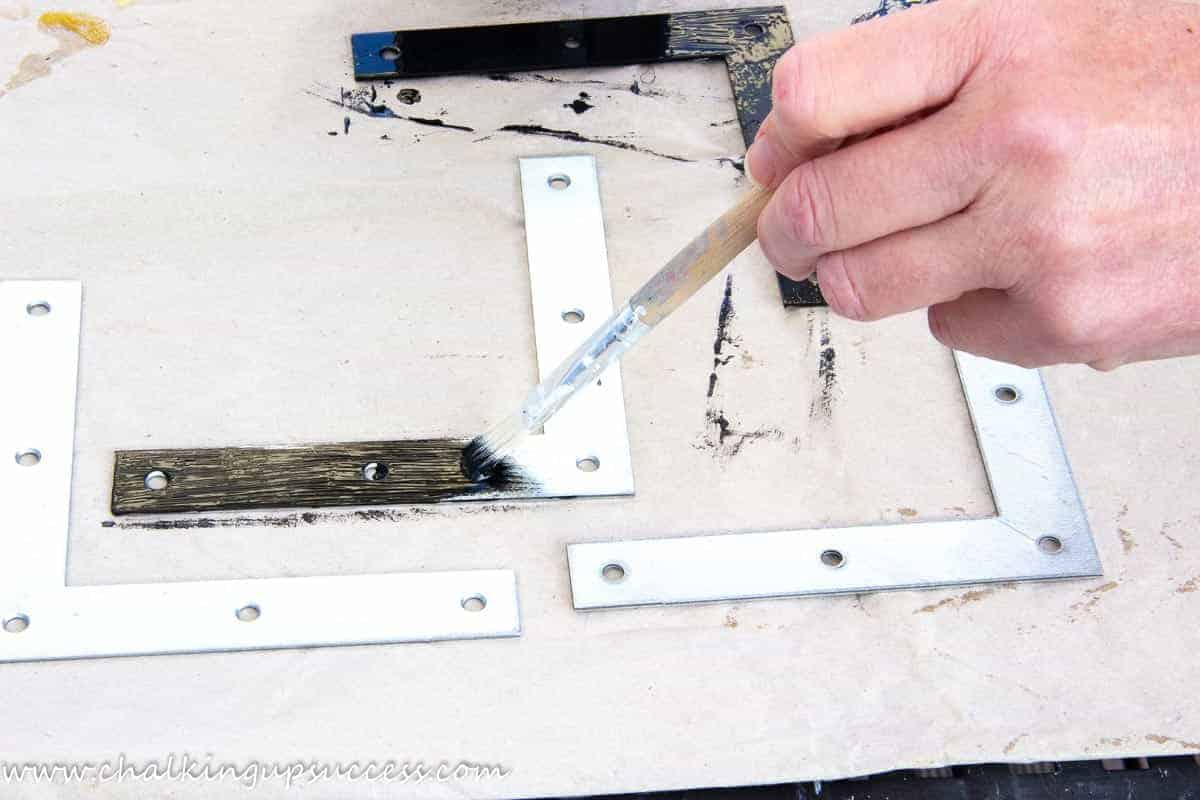 A hand using a small paintbrush to paint four galvanized L-shaped corner brackets with black paint for metal.