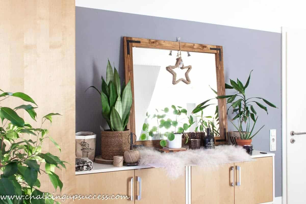 A photo of the DIY wood framed mirror resting against the wall in a craft room.