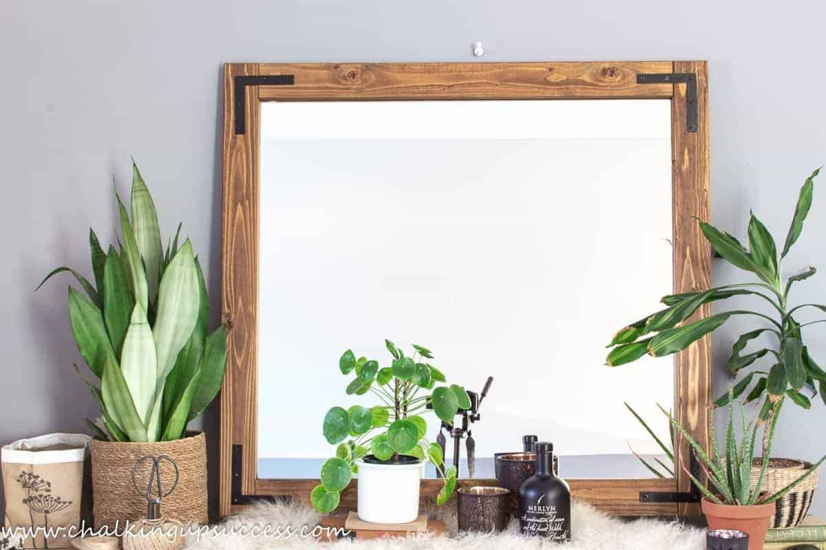 A large square industrial style wood framed mirror.