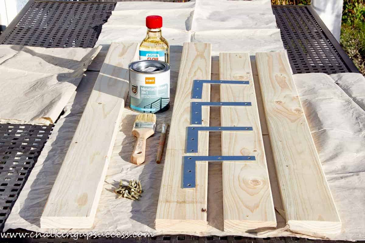 Supplies needed for making a DIY wood framed mirror - four pieces of wood, L-shaped brackets, metal paint in black, paintbrushes, wood stain and screws.
