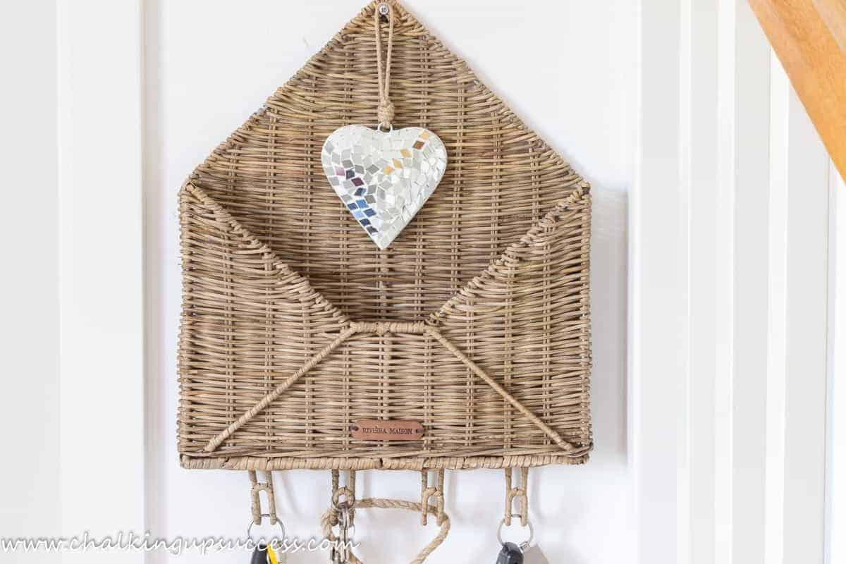 A wicker post basket in the shape of an open letter is attached to the wall next to the staircase.