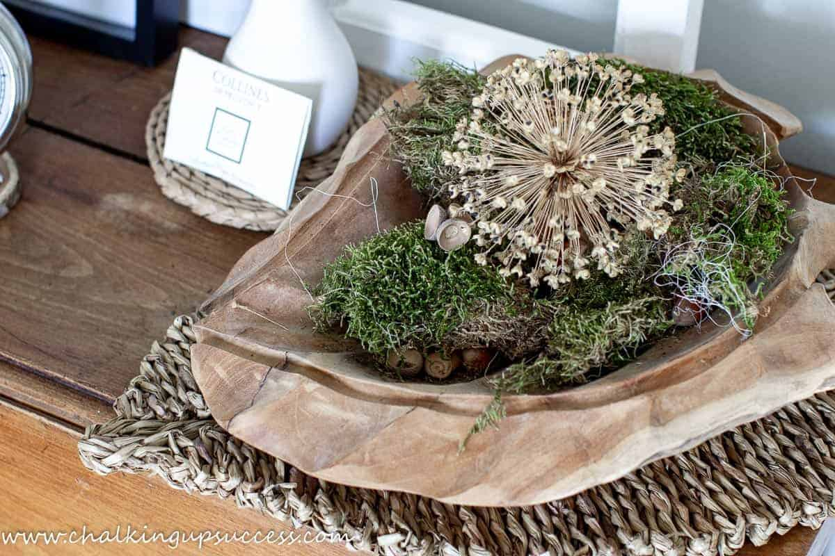 A leaf shaped wooden bowl filled with moss, acorns and a large, round Allium seedhead.