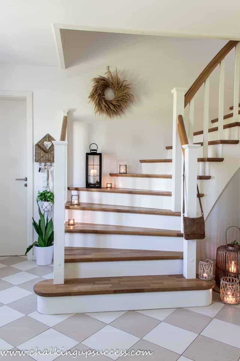 A view of the white and wood staircase after the hallway refresh. Black metal lanterns are burning on the stair treads and three rattan lanterns in varying sizes are burning at the bottom of the stairs.