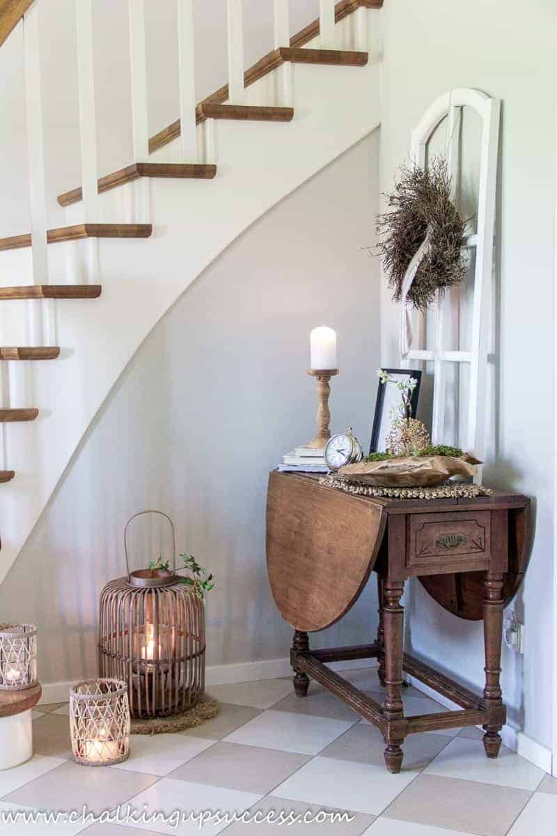 A side view of the white and wood stairs after the hallway refresh with three rattan lanterns at the foot. A brown wooden vintage table is decorating with a brown twig wreath attached to a large white window frame.