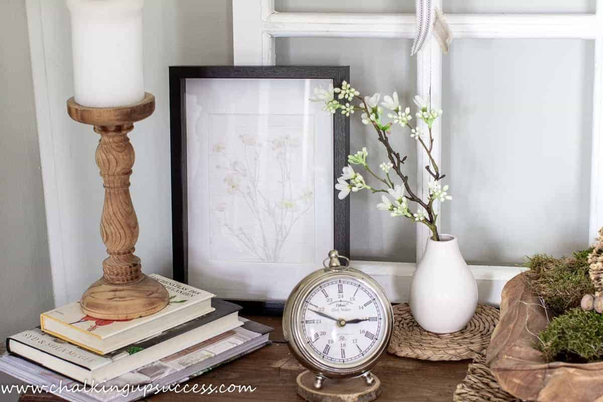Decor on the vintage French table include a brown wood candlestick placed on a stack of books, A DIY pressed flower pring, a silver clock, a small white vase with a white and green flowering branch and a wooden bowl in the shape of a leave filled with moss and acorns.