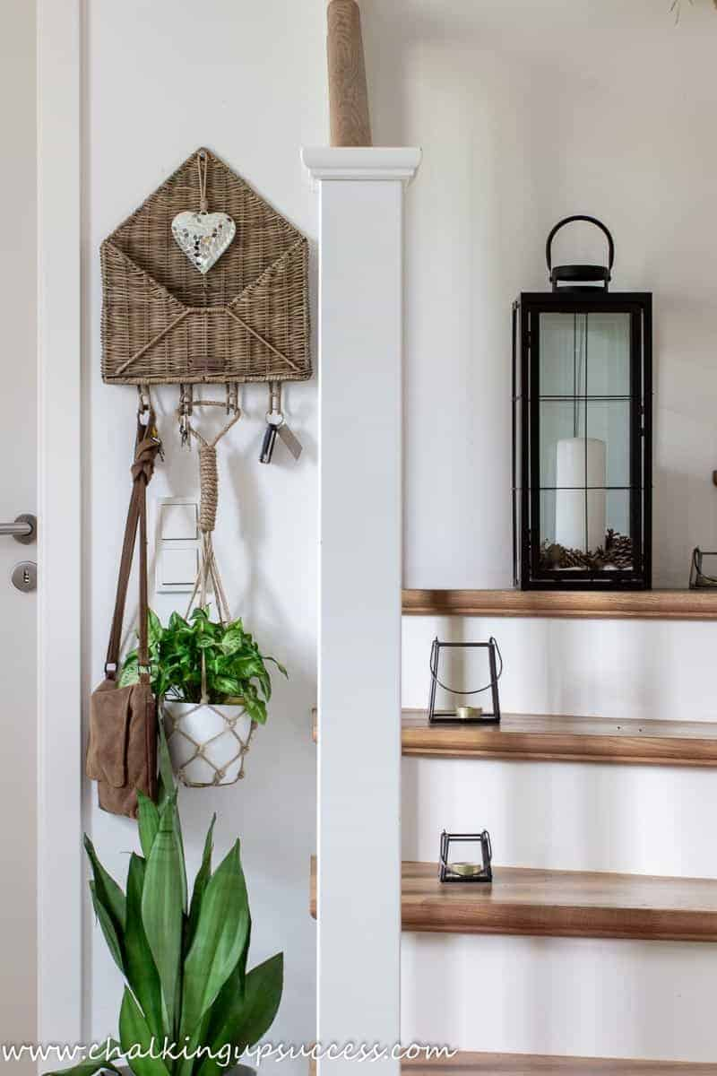 Wood and white staircase. Black metal lanterns are on the side of each stair and on the wall is a large dried grass wreath. Attached to the wall to the left of the staircase is a rattan post basket in the shape of an open envelope.