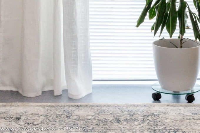 Showing the bottom third of white linen curtains. The hem is hovering just above the floor. To the right of the curtains is a green Dragon Tree in a white ceramic plant pot. hang curtains properly.