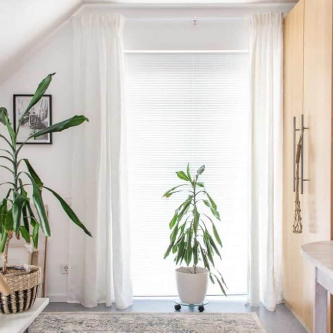 White linen curtains hung on a white curtain rod. The curtains are hung 10cms from the ceiling and the bottom of the curtains hover slightly above the floor.