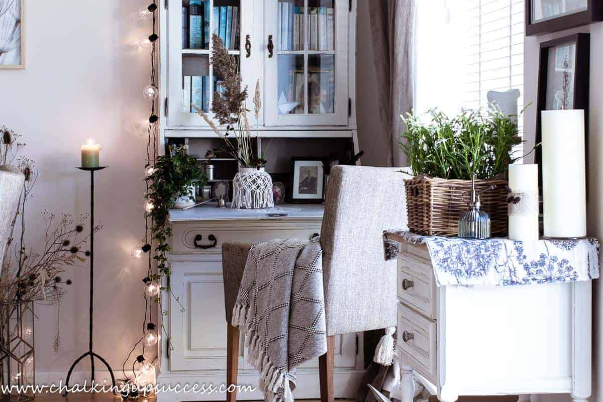 Festoon lights are hanging from the side of a white and grey secretary desk. A wrought iron candle stand holding a lit candle, is standing at the side of the desk.