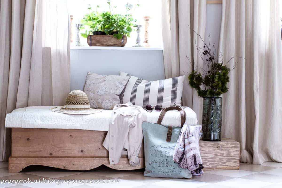 The summer home tour begins in the hallway. A wooden chest serves as a bench. Resting on the bench is a straw sunhat and a pair of sunglasses. White summer flowers fill a wooden box sitting on the windowsill in the sunshine.