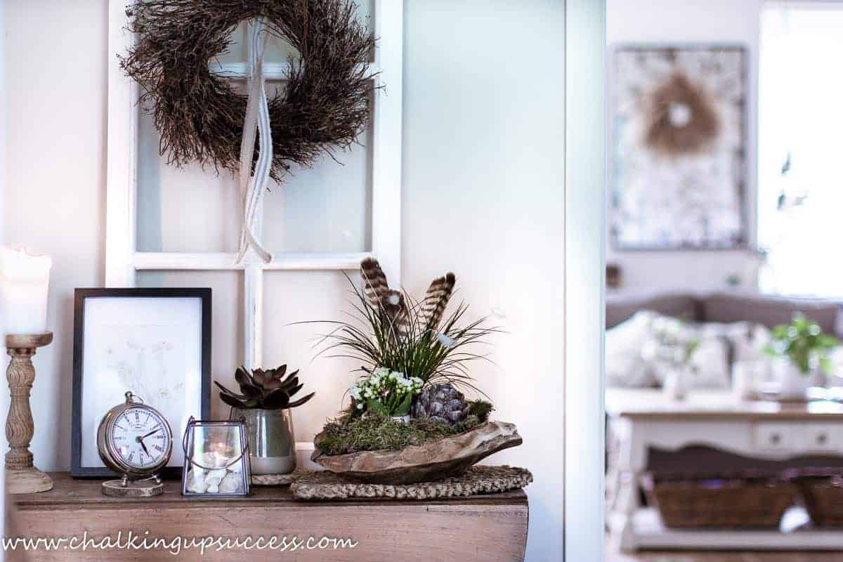 For the summer home tour, a console table decorated for summer with a large wooden bowl filled with a small grass plant, shells, and a small white flowering plant.