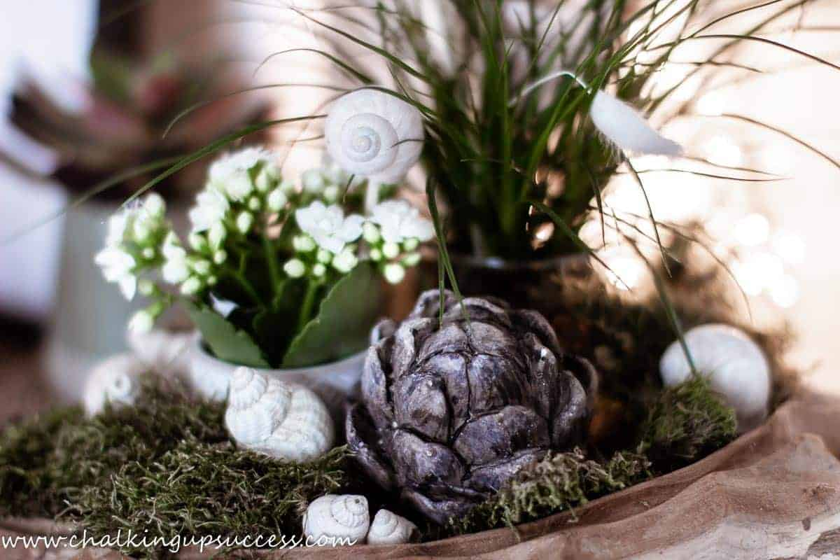 A wooden bowl filled with summer decor. A small flower pot filled with a white flowering plant, shells, a coastal grass plant and a wooden artichoke. Moss is tucked in, all around the decor.
