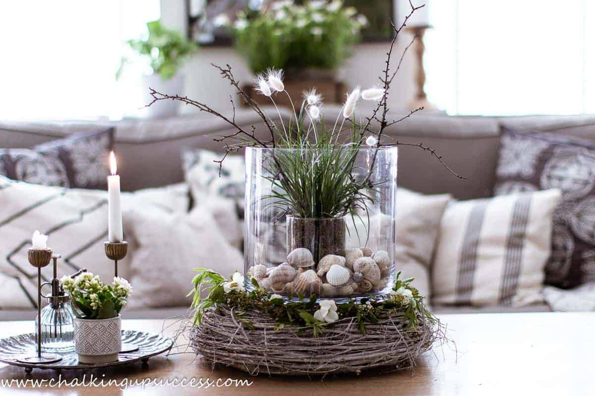 For a summer home tour centrepiece a large glass cylinder vase rests on top of a thick rustic twig wreath. The cylinder vase is filled with a grass plant, bunny tail grass and twigs. The bottom of the vase is filled with seashells.