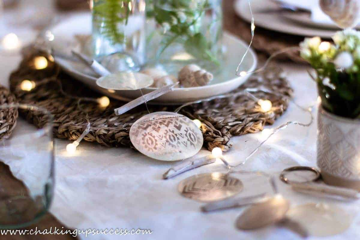 Coastal table decor. showing glass bottles filled with water and green foliage and a candle in the neck of the bottle.  Driftwood and faux mother of pearl decor has been draped along the table.