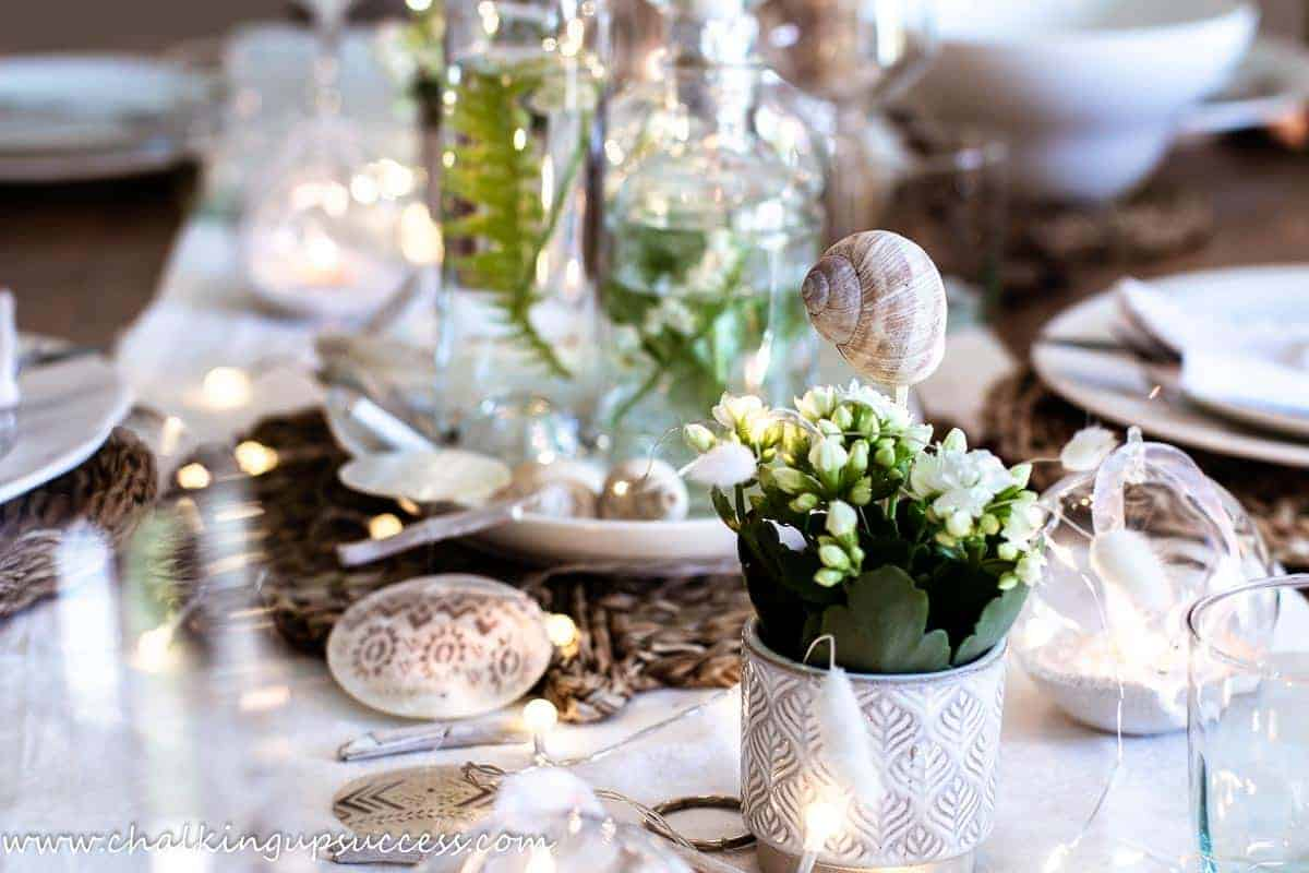 A coastal tablescape showing glass bottles filled with water and green foliage and a candle in the neck of the bottle. Decorated for the 2021 summer home tour.
