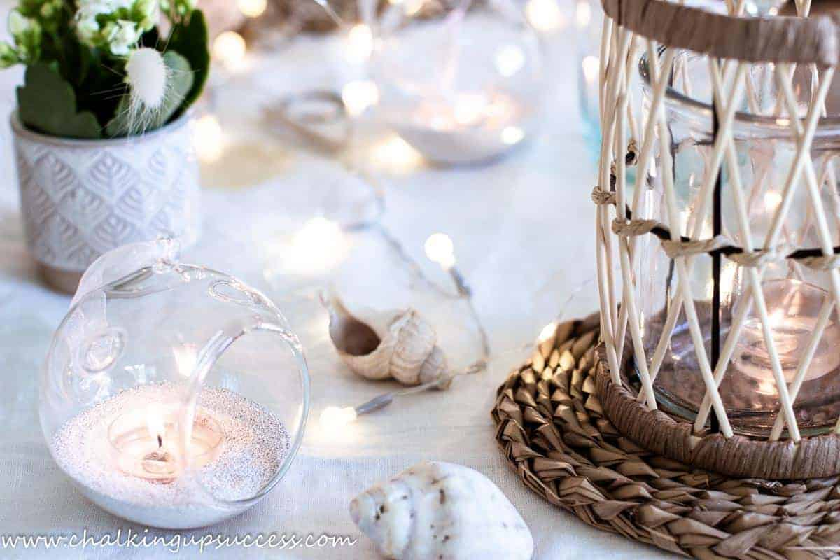 A coastal tablescape with shells, rattan lanterns and round glass globe tealights filled with sand and a candle.
