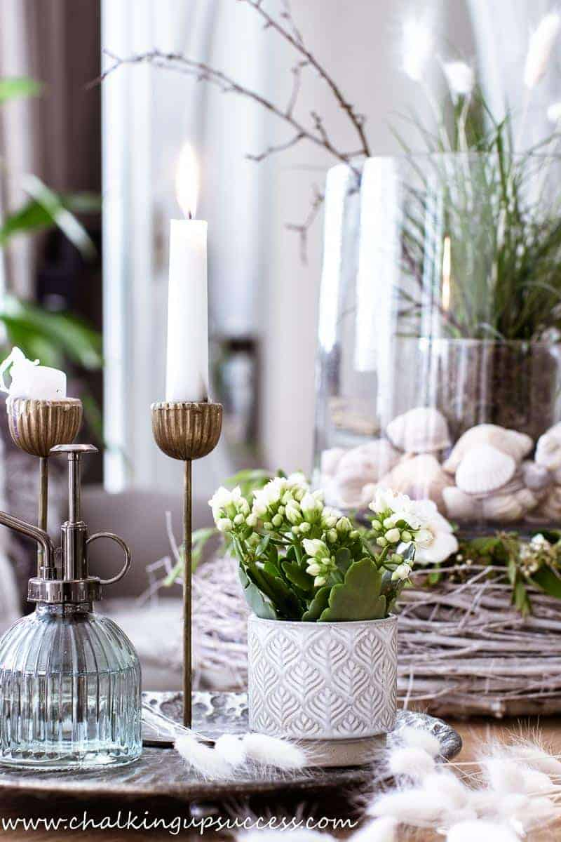 A side view of the summer decoration on the coffee table. A metal tray filled with candles, white flowering plants and a pretty glass and metal plant sprayer. In the background is the centerpiece with shells and grasses - summer home tour 2021
