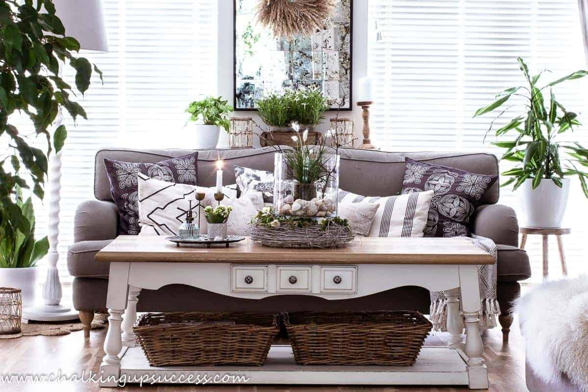 A front view of a wood and white table in front of a brown sofa. On the table is a centrepiece made from shells, grasses and a rustic twig wreath. Perfect decor for a coastal style summer home tour.