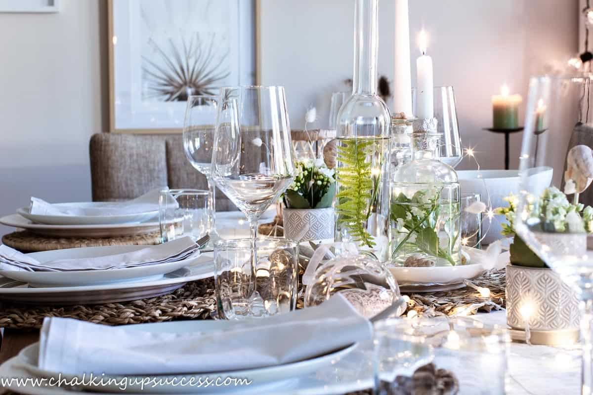 A view of a dining table set for summer dining. Filled with candles and rattan lanterns. Summer home tour 2021.