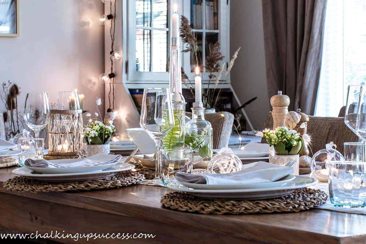 A summer tablescape with three glass bottles filled with water and fern fronds as a centerpiece. In the neck of each bottle sits a lit candles.