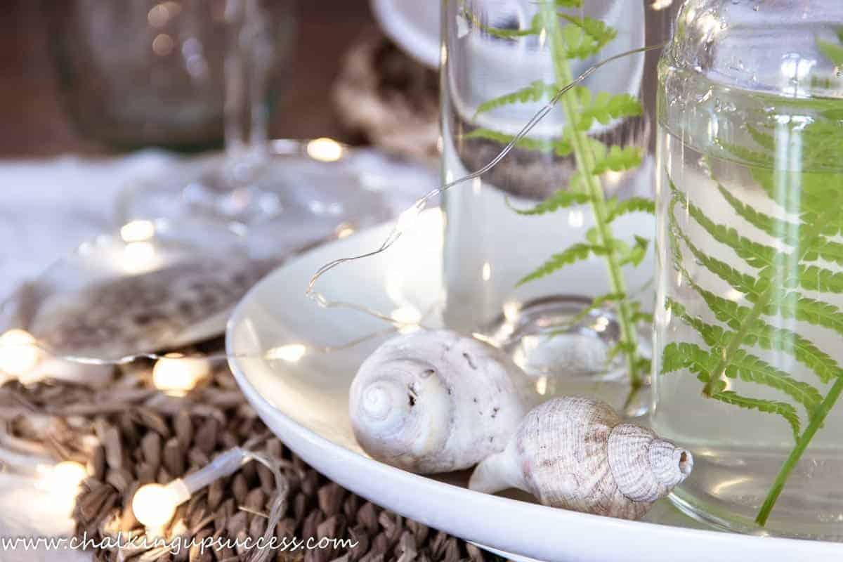 A close-up image of two glass bottles on a white place with shells placed all around - decorate your home for summer