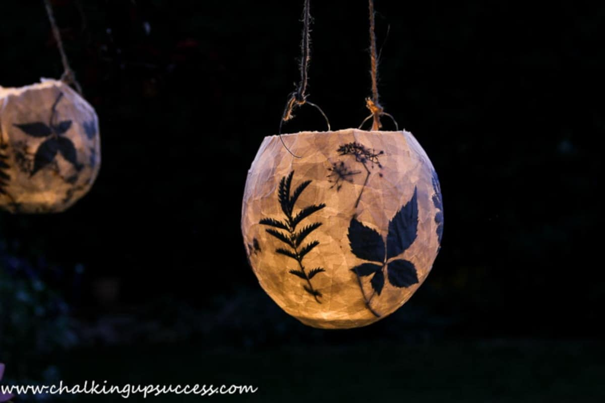 paper mache lanters made with pressed flowers, hanging in a tree at night.