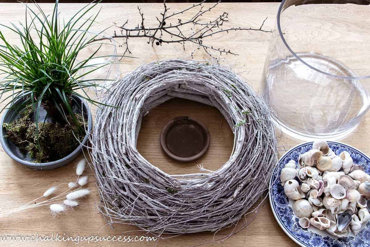 A large twig wreath, large cylinder vase, seashells, grasses and moss
