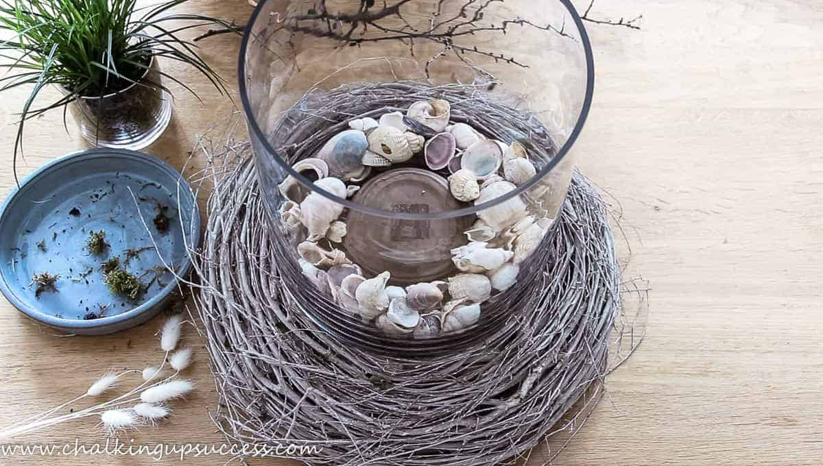 A large cylinder vase filled with seashells sits on a twig wreath