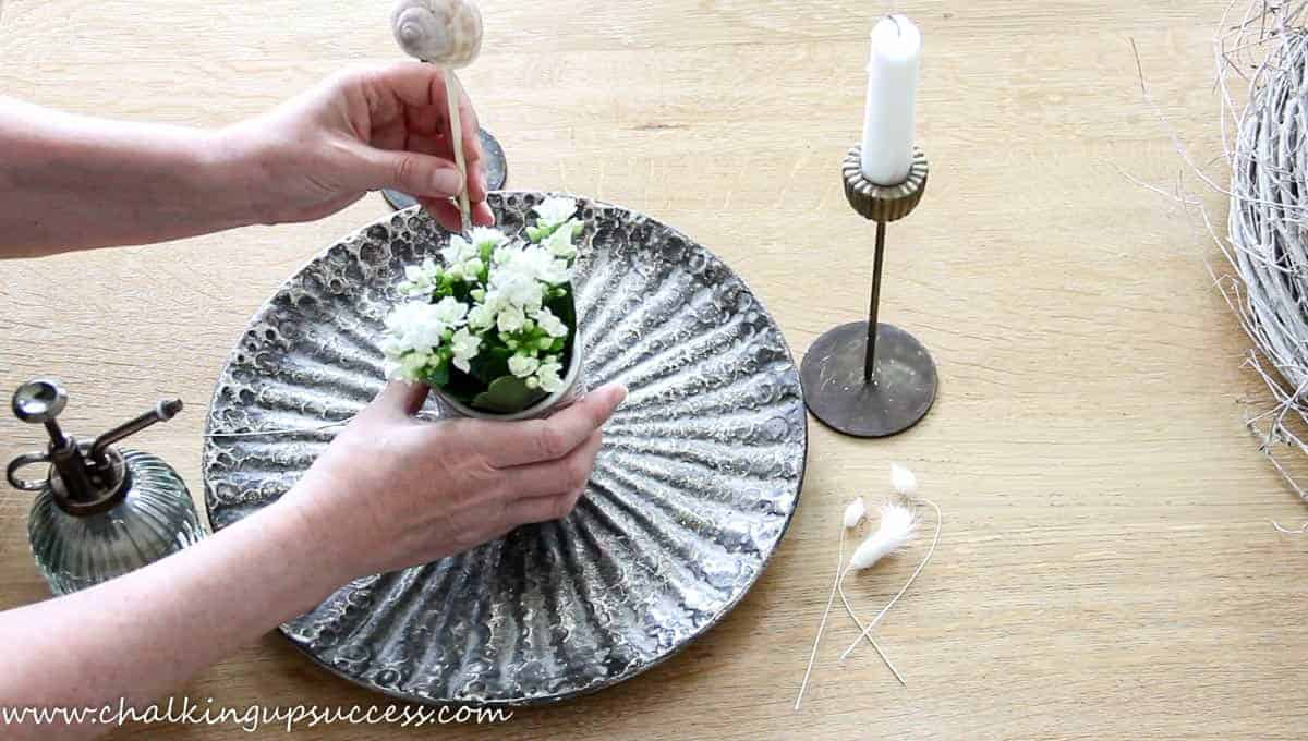 A person decorating a metal tray with a white flowered plant