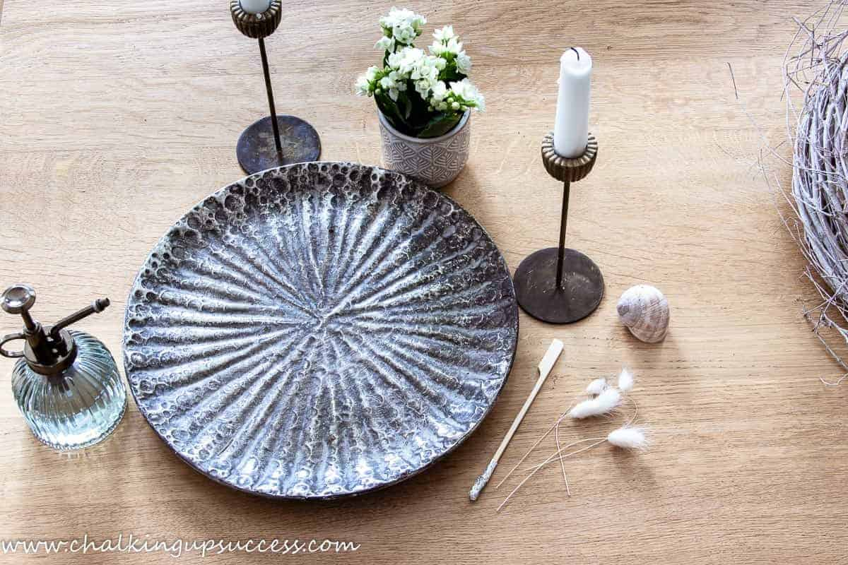 Decorate your home for summer with a metal tray filled with a white flowering plant, candlesticks, and a glass plant mister