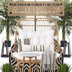 This outdoor furniture for small spaces includes a high back rattan loveseat with large white, padded seat covers. Accessories include white striped square and lumbar pillows, a round black and tan geometiric rug, a wood and marble side table, black metal lanterns and green plants in large metal containers. Over the loveseat is a black sun umbrella with integrated lights.