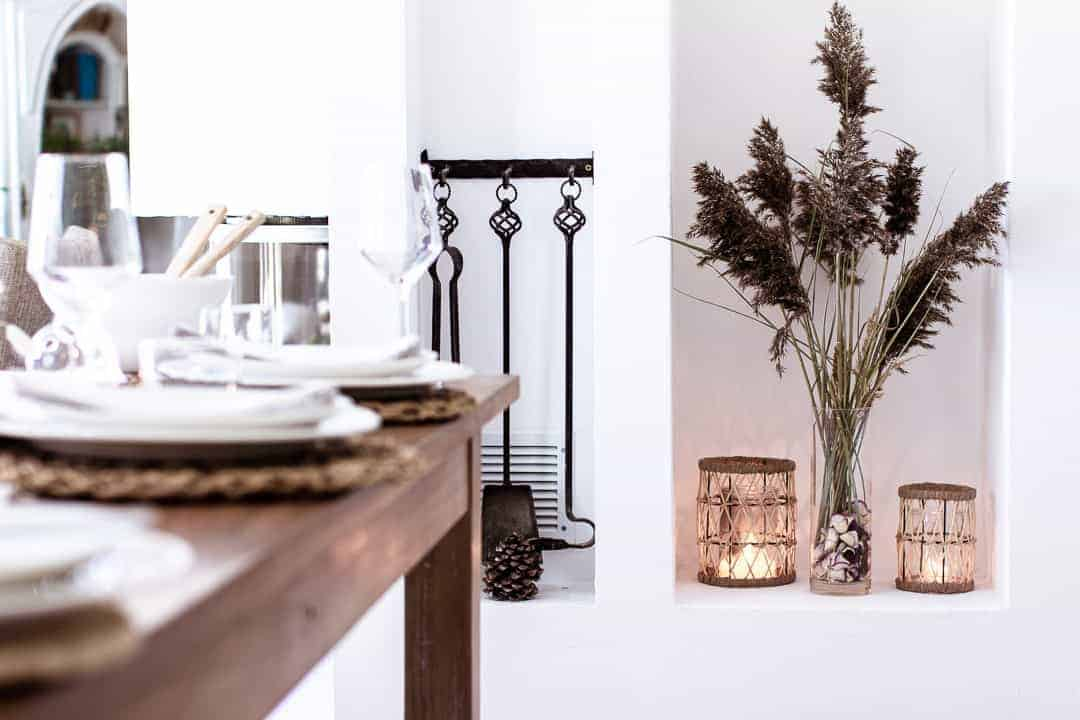 A display of tall dried grasses inside a tall cylinder vase. The displaye sits in a white alcover and is surrounded by lit rattan storm lanterns - very pretty!